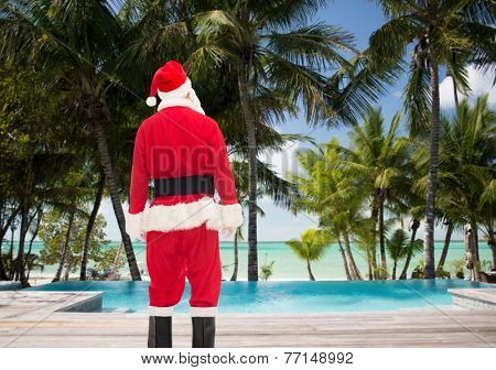 christmas, holidays and people concept - man in costume of santa claus from back over tropical beach and swimming pool background