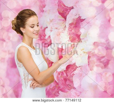 engagement, celebration, wedding and people concept - smiling woman in white dress wearing diamond ring over pink floral background