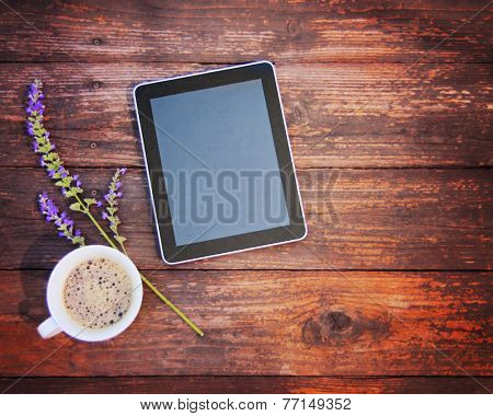 electronic tablet device on a wooden workspace table with coffee and flower