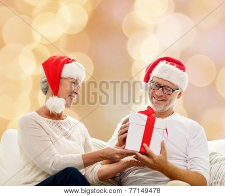 family, holidays, christmas, age and people concept - happy senior couple in santa helper hats with gift box over beige background