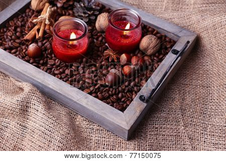 Candles on vintage tray with coffee grains and spices, bumps on sackcloth background