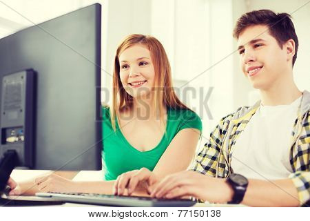 education, technology, school and people concept - two smiling students having discussion in computer class at school