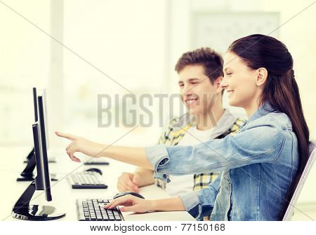 education, technology and school concept - two smiling students in computer class, girl pointing finger at screen