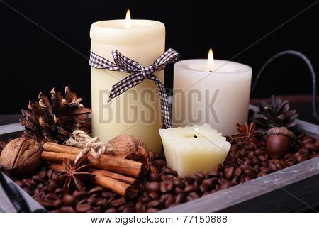 Candles on vintage tray with coffee grains and spices, bumps on wooden table, on dark background