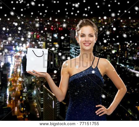 luxury, advertisement, holydays and sale concept - smiling woman with white blank shopping bag over snowy night city background