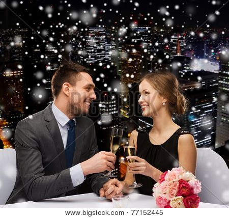 celebration, christmas, holidays and people concept - smiling couple clinking glasses of sparkling wine at restaurant over snowy night city background