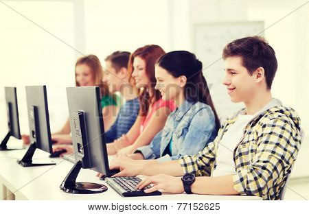 education, technology, friendship and school concept - smiling male student with classmates in computer class
