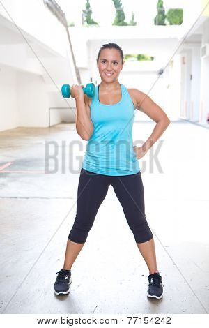 Beautiful woman exercising with dumbbell for her bicep, outdoor