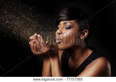 Black Woman Blowing Golden Dust