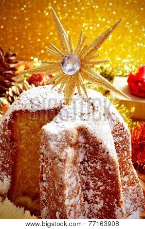 closeup of a pandoro, a typical Italian sweet bread for Christmas time, on a table with christmas ornaments and gifts