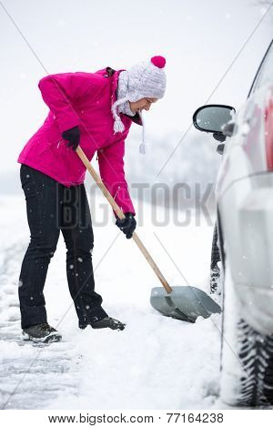 Woman  shoveling and removing snow from his car during a snowing
