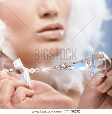 Closeup photo of luxury crystal gem held by woman. Focus on crystal.