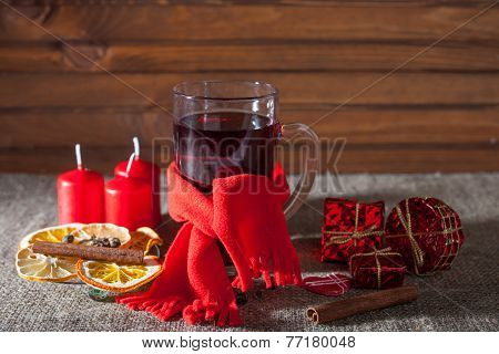 mulled wine in a glass with spices, ginger, lemon, cinnamon and fruit on a wooden background