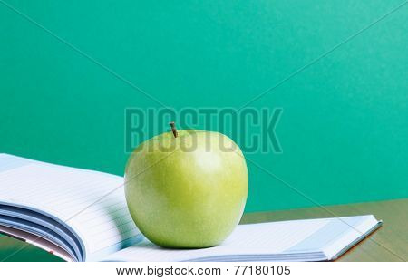 A green apple on an open exercise book
