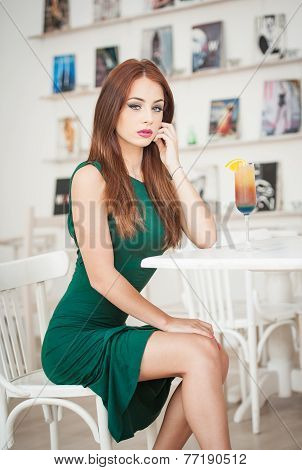 Fashionable attractive young woman in green dress sitting in restaurant. Beautiful redhead posing