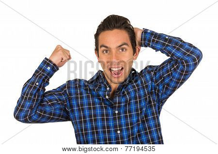 handsome young cheerful latin man wearing a blue plaid shirt posing with fist up