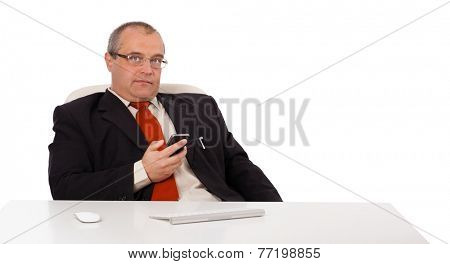 businessman sitting at desk and holding a mobilephone with copys pace, isolated on white