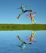 couples jump on grass and water