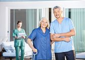 stock photo of male nurses  - Portrait of confident male caretaker and disabled senior woman with female nurse in background at nursing home yard - JPG