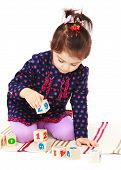 picture of montessori school  - Little girl plays cubes sitting on the floor - JPG