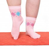 stock photo of zumba  - Overweight woman in funny socks excercising on red carpet - JPG