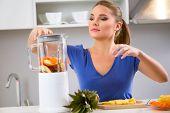 stock photo of juicer  - woman making juice using juicer machine - JPG