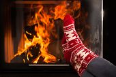 picture of frozen  - Woman heating frozen feet by warm fireplace - JPG