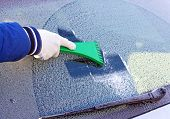 stock photo of ice-scraper  - scraping the windshield of a car at winter - JPG