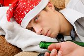 image of sad christmas  - Sad and Tired Teenager with Bottle of the Beer and Santa Hat on the Sofa at the Home - JPG