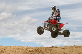image of four-wheelers  - A 4-wheeler jumps at a motocross track.