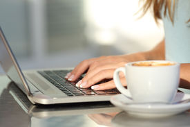 picture of hands up  - Close up of a woman hands typing in a laptop in a coffee shop terrace in the street