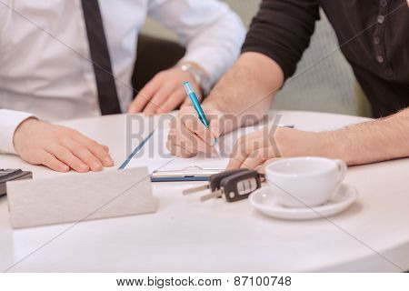 Close up of a male customer signing the contract