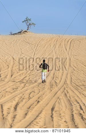 Man seen by back and running on a sand road