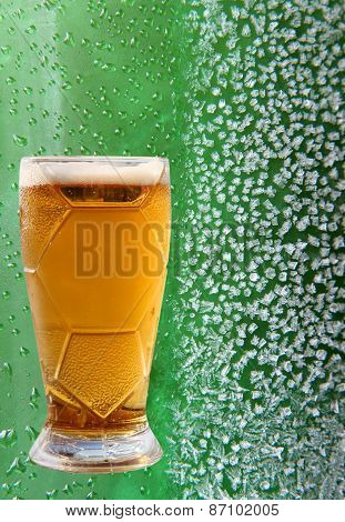 Beer Glass On Ice Crystals And Drips Green Background.
