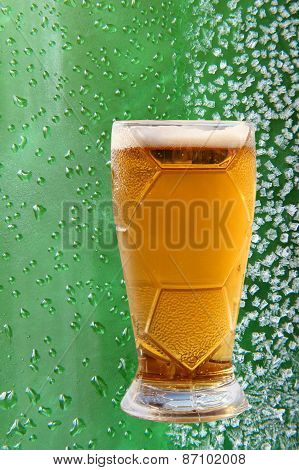 Froth Beer Glass On Ice Crystals And Drips Green Background.