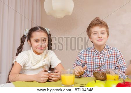 Cute kids have a meal at home