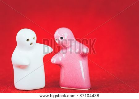 Two Ceramic Doll On Red Fabric