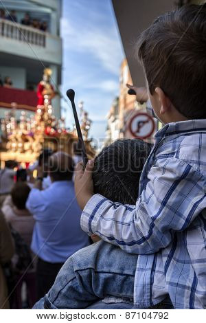 Child Of Backs With Ramrod Of Drum In His Hand With His Father During Holy Week Procession, Spain