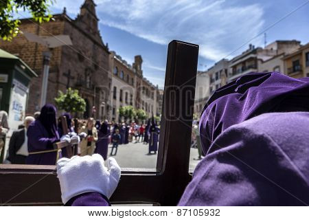 Penitent praying on his cross in front of church during Holy week procession Spain