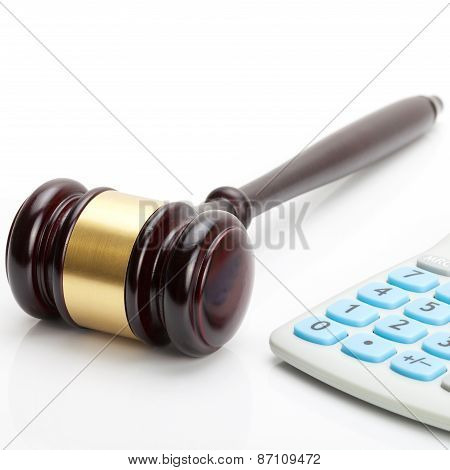 Wooden Judge's Gavel And Calculator Next To It