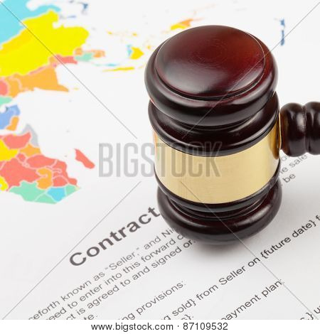 Wooden Judge's Gavel Over World Map And Contract