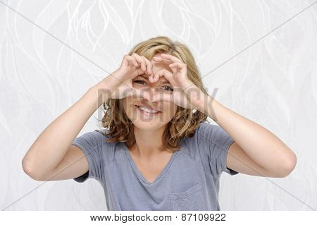 Smiling young woman making heart with fingers