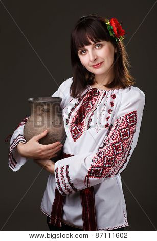 beautiful woman in an embroidered shirt with a jug in his hands