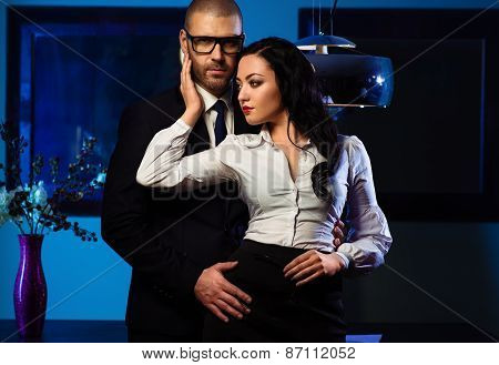Couple Indoors. Sensual Brunette And Handsome Businessman Hugging Indoors. Office Romance Concept
