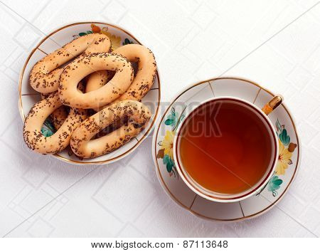 bagels with poppy seeds and a cup of tea on the tablecloth