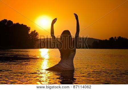 Silhouette of young beautiful woman in the river over sunset sky. Female perfect body contour