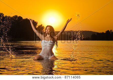 Sexy brunette woman in wet white lingerie posing in river water with sunset on background