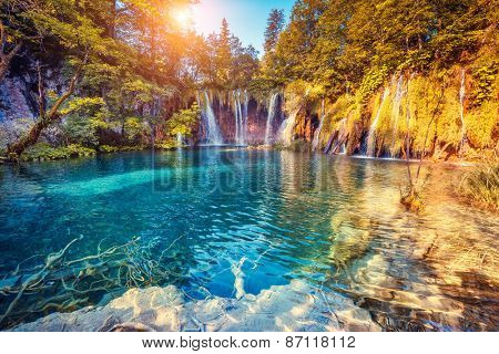 Majestic view on turquoise water and sunny beams in the Plitvice Lakes National Park. Croatia. Europe. Dramatic unusual scene. Beauty world. Retro filter and vintage style. Instagram toning effect.