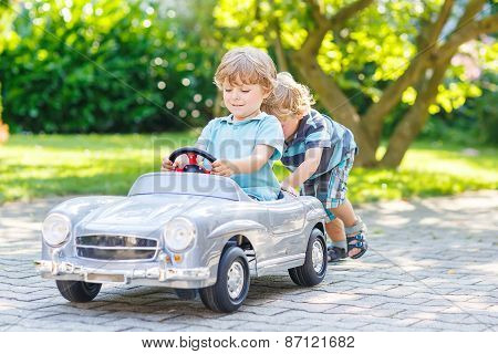 Two Funny Little Friends Playing With Big Old Toy Car