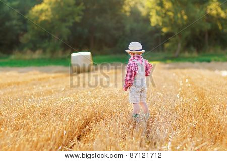 Funny Little Toddler Boy In Leather Shors, Walking  Through Wheat Field